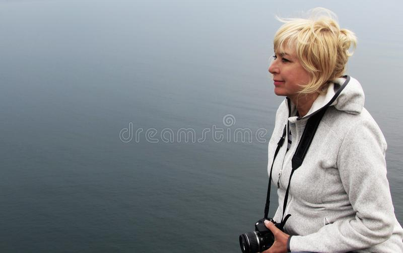 Woman on a background of boundless sea, the concept of a healthy and active lifestyle in senior adults royalty free stock image