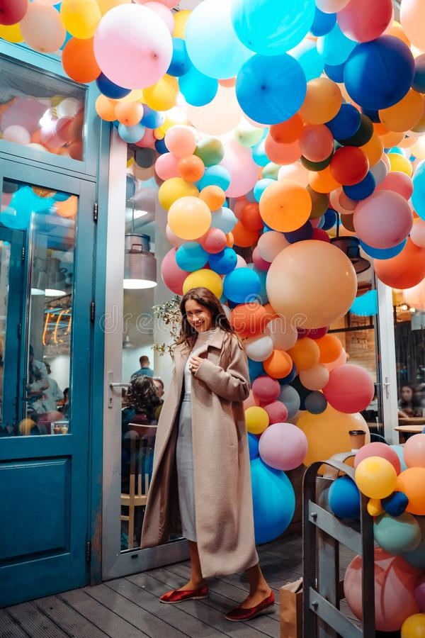 Woman on the background of wooden door with balloons royalty free stock photo