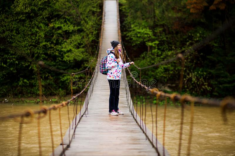 Woman with backpack hiking Lifestyle adventure concept forest and cross river in forest. Active vacations into the wild royalty free stock photography