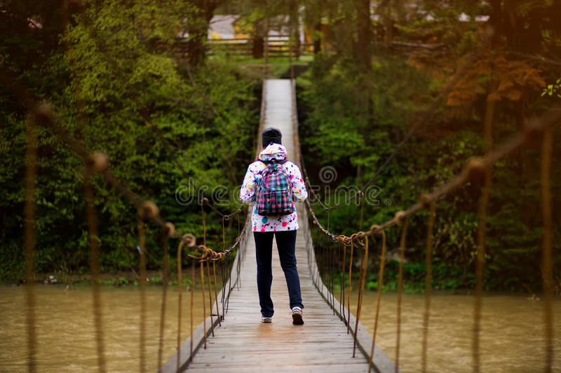 Woman with backpack hiking Lifestyle adventure concept forest and cross river in forest active vacations royalty free stock photography