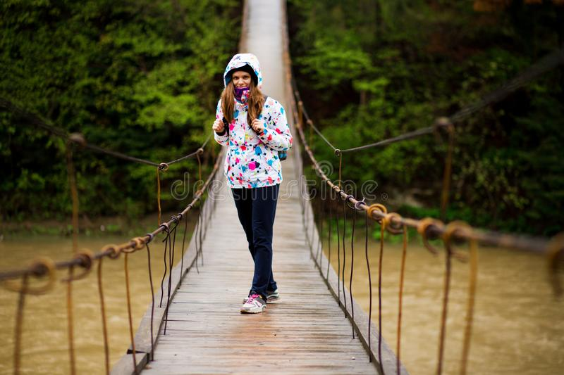 Woman with backpack hiking Lifestyle adventure concept forest and cross river in forest royalty free stock images