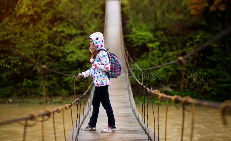 Woman with backpack hiking Lifestyle adventure concept forest and cross river in forest. Active vacations into the wild stock images