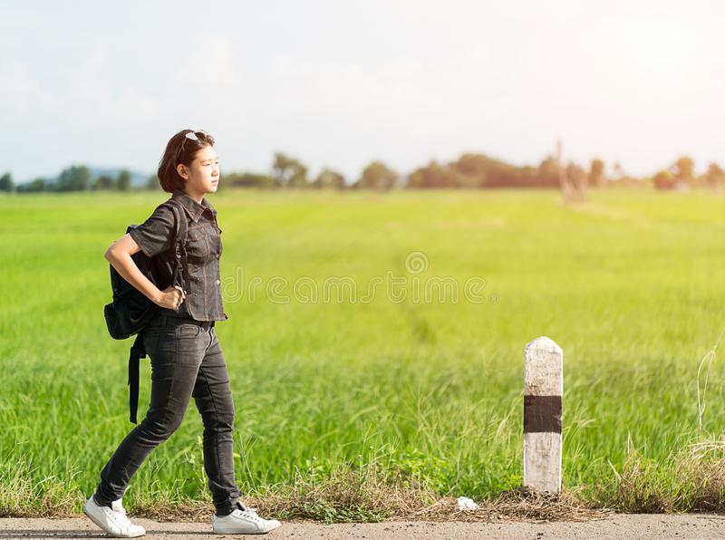 Woman with backpack hitchhiking along a road. Young asian woman short hair and wearing sunglasses with backpack hitchhiking along a road in countryside Thailand stock image