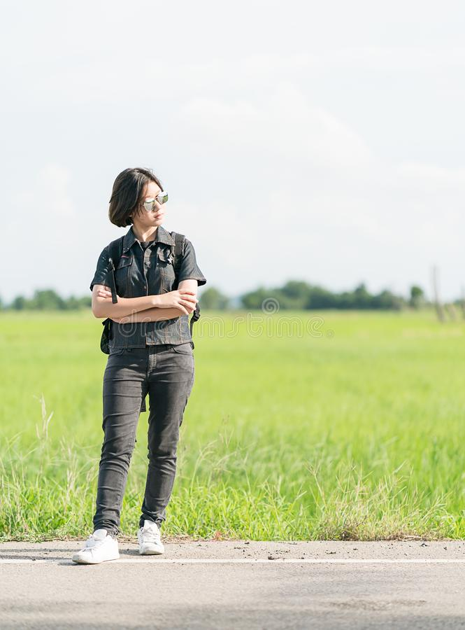 Woman with backpack hitchhiking along a road. Young asian woman short hair and wearing sunglasses with backpack hitchhiking along a road in countryside Thailand royalty free stock photo