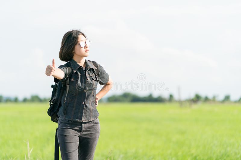 Woman with backpack hitchhiking along a road. Young asian woman short hair and wearing sunglasses with backpack hitchhiking along a road in countryside Thailand royalty free stock photos