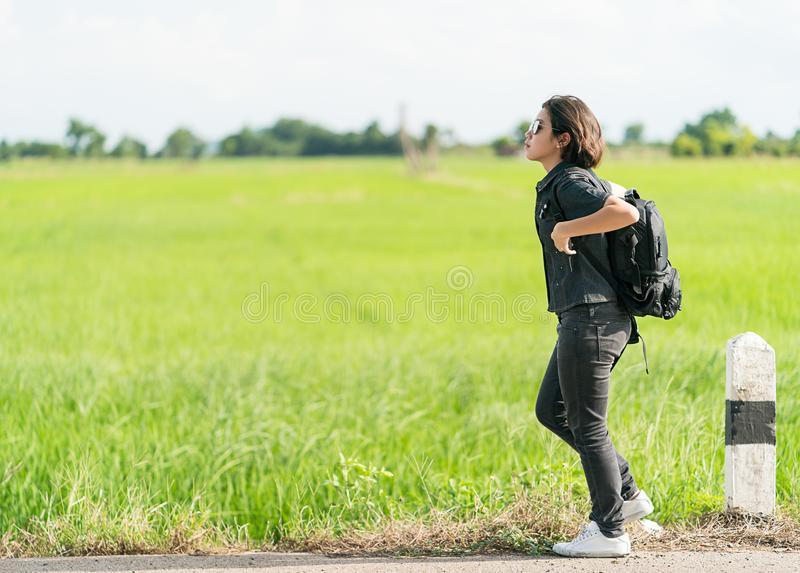 Woman with backpack hitchhiking along a road. Young asian woman short hair and wearing sunglasses with backpack hitchhiking along a road in countryside Thailand stock photo
