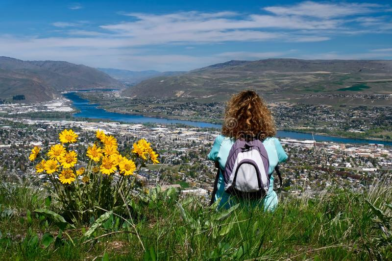 Woman with backpack sitting on the top of mountain enjoying scenic views of city and river. Spring wild flowers on hills. Wenatchee. Washington. United States stock photography