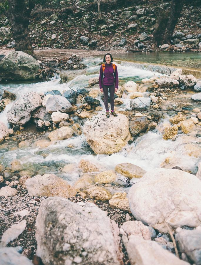 A woman with a backpack is standing near a mountain river stock image