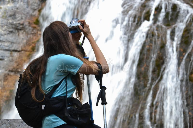 Woman with backpack taking photo of waterfall royalty free stock image