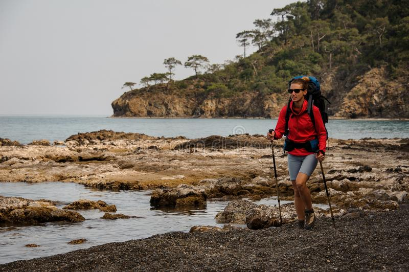 Woman with backpack travelling on a sea coast stock image
