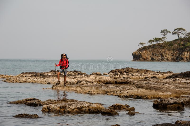 Woman with backpack travels on a sea coast stock photos
