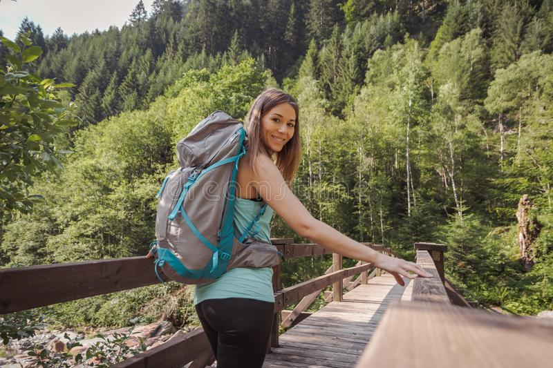 Woman with a backpack walking on a bridge into the forest royalty free stock image