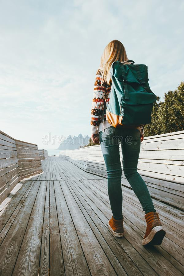 Woman with backpack walking on wooden bridge stock images