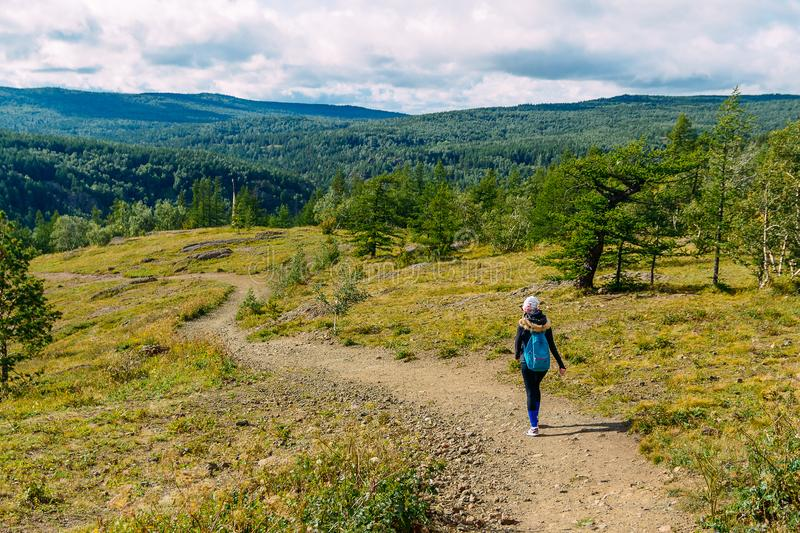 Woman with backpack walks along footpath with mountain royalty free stock image