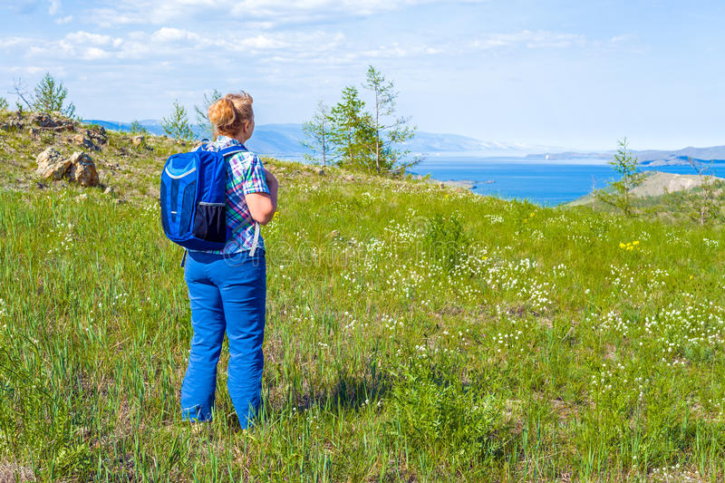 Woman backpacker came to a large lake stock image