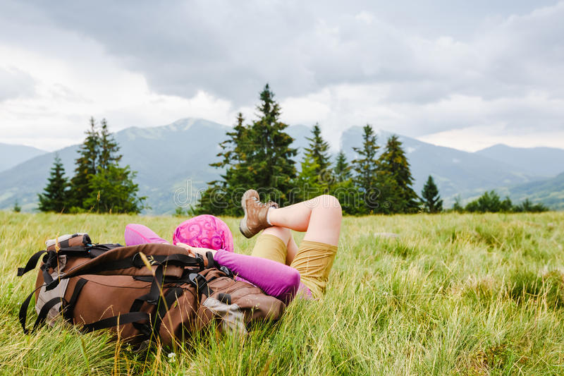 Woman backpacker enjoy the view. On green summer mountains stock photo