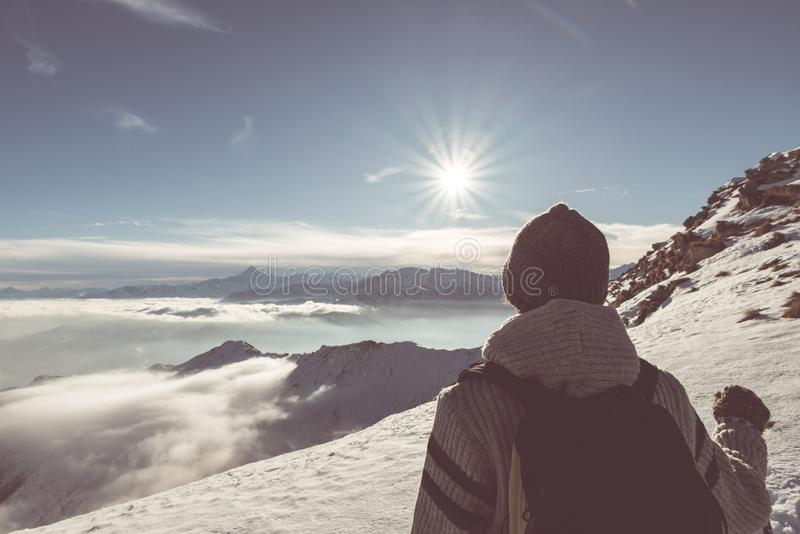 Woman backpacker hiker looking at view high up on the Alps. Rear view, winter cold snow, sun star in backlight, split toning, desa stock photo