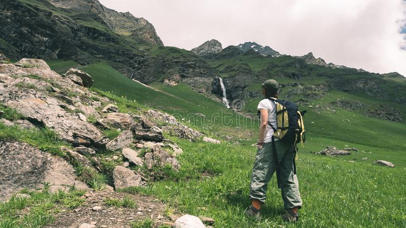 Woman Backpacker hiking in idyllic landscape, waterfall and blooming meadow. Summer adventures and exploration on the Alps. Toned. royalty free stock photos