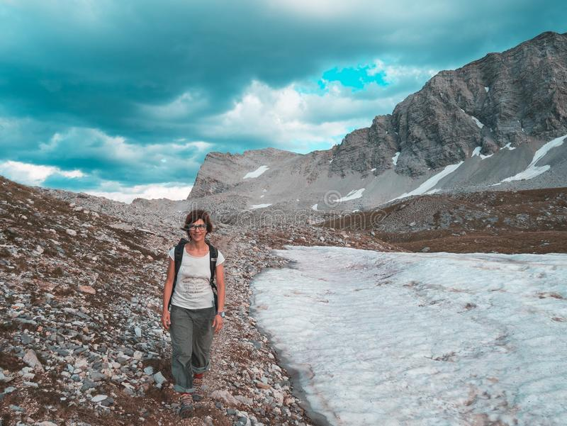 Woman Backpacker hiking in idyllic landscape, waterfall and blooming meadow. Summer adventures and exploration on the Alps. Toned. royalty free stock photo