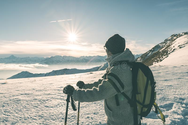 Woman backpacker with hiking poles looking at view high up on the Alps. Rear view, winter cold snow, sun star in backlight, split royalty free stock image