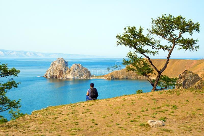 A woman backpacker looks at the Shamanka Rock, Cape Burhan on Olkhon Island. Lake Baikal, Russia. royalty free stock photography