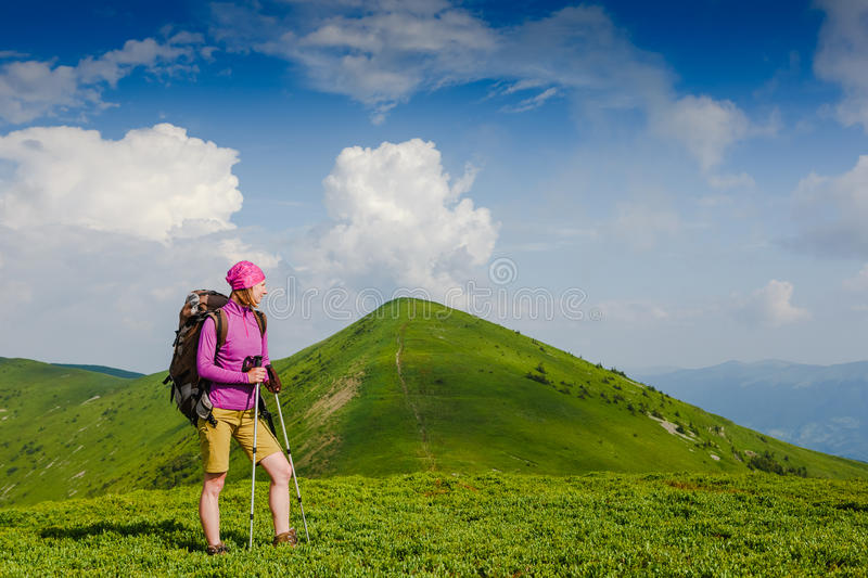 Woman backpacker in the mountains enjoy the view. Woman backpacker in the summer mountains enjoy the view stock photos