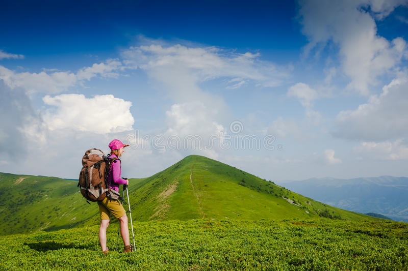 Woman backpacker in the mountains enjoy the view. Woman backpacker in the sunny mountains enjoy the view stock photo