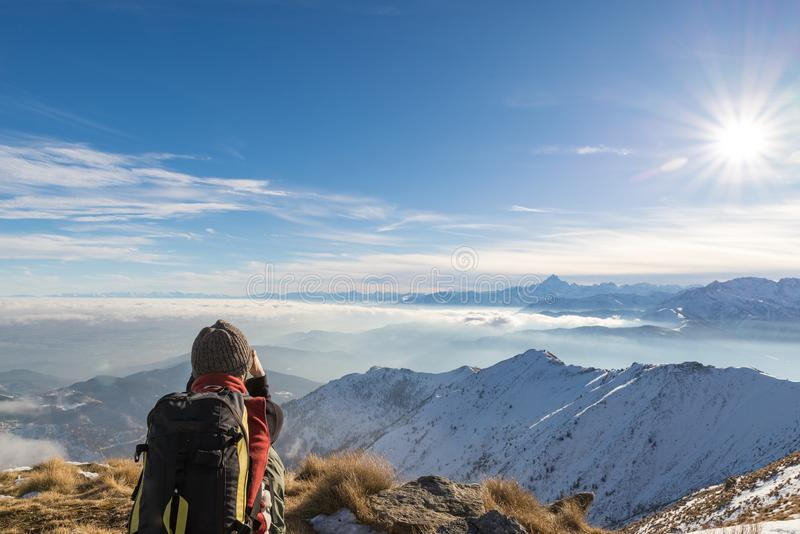 Woman backpacker resting on mountain top. Rear view, winter lifestyle, cold feeling, sun star in backlight royalty free stock photo