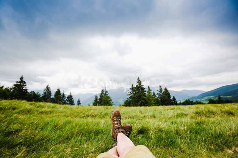 Woman backpacker`s feet in boots on green summer mountains royalty free stock images
