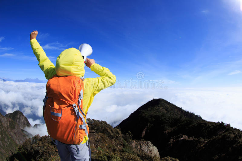 Woman backpacker shouting with loudspeaker on beautiful mo stock photos