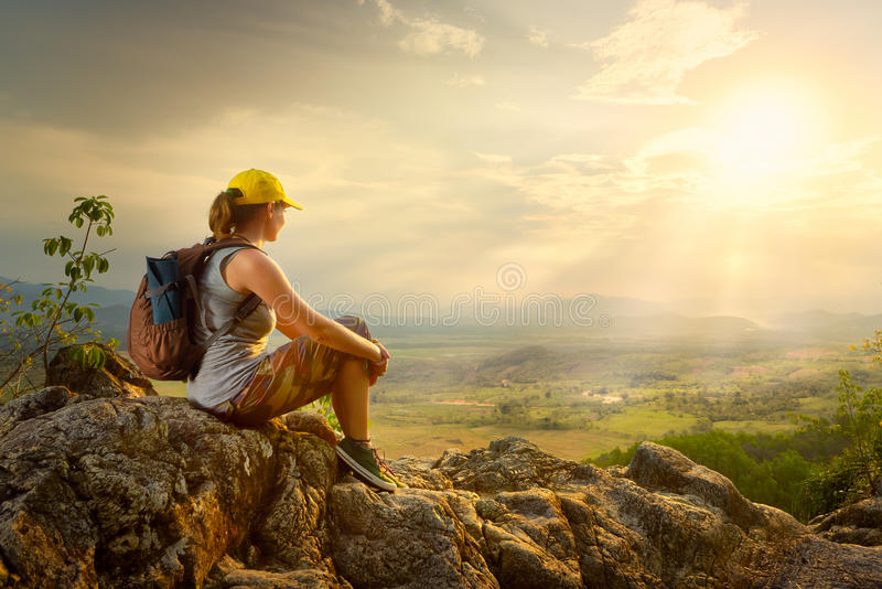 woman with backpacker sitting on top of the mountain and enjoying valley view. stock photos