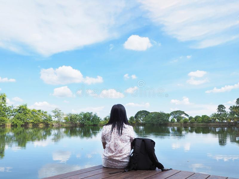 Woman backpacker tourist sitting on wood in front of river stock images