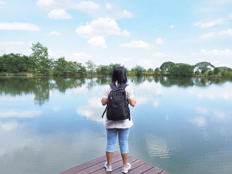 Woman backpacker tourist standing on wood in front of river stock photos