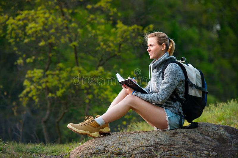 Woman backpacker writing notes hiking in summer forest and stopp stock photography