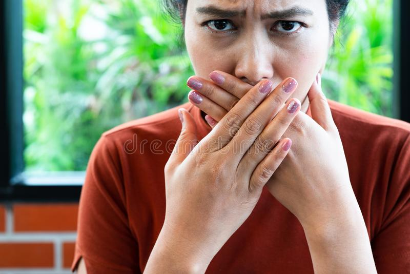 Woman with bad breath covering mouth, halitosis concept stock photos