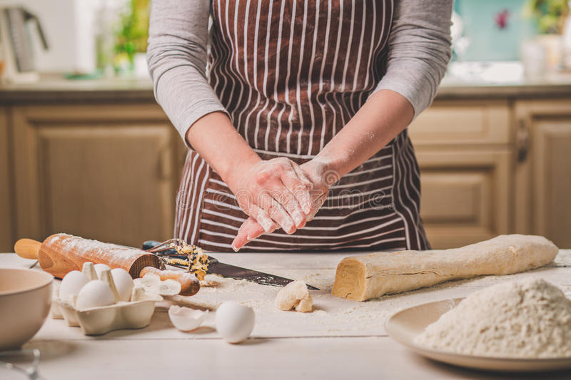 Woman bake pies. Confectioner makes desserts. Making buns. Dough on the table. Knead the dough. royalty free stock photography