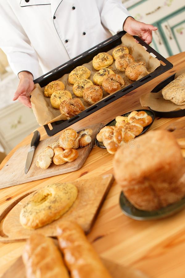 Woman with baked goods. Woman hands holding baking tray with homemade baked goods royalty free stock photography