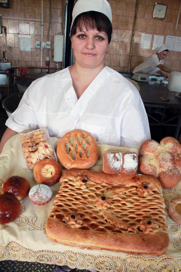 Woman baker with bread products in bakery stock images