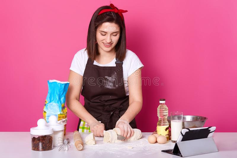 Woman baker cuts dough in small parts, ready for sculpting hot cross buns, make pies from dough, wears brown apron, casual white t royalty free stock photos