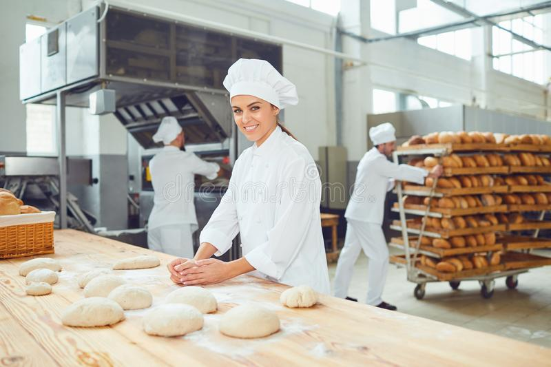 A woman baker smileswith colleagues at a bakery. A women baker smiles with a dough in her hands with colleagues at a bakery stock photo
