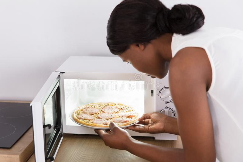 Woman Baking Pizza In Microwave Oven stock images