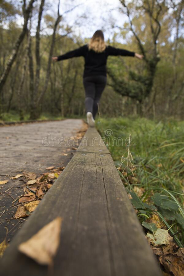 Woman balances on a log. Young woman balances on wooden walkway in a green, lush and dark forest on a cold autumn day in Ireland stock image