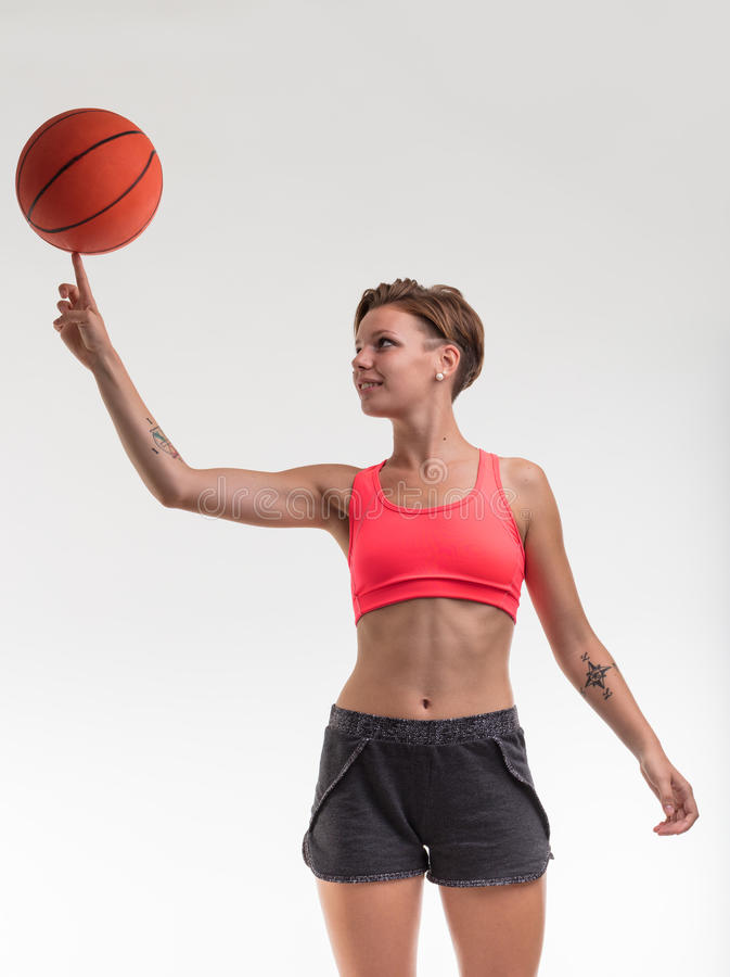Woman balancing a basketball on her finger stock images