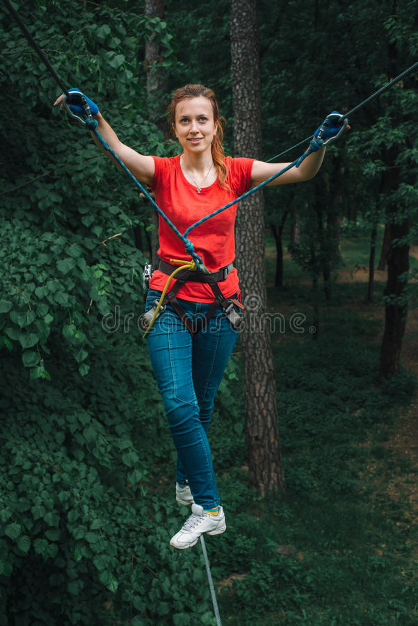 Woman balancing on high in forest adventure rope park royalty free stock image