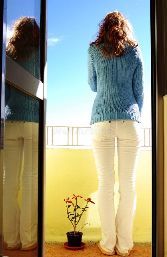 Woman on balcony royalty free stock image