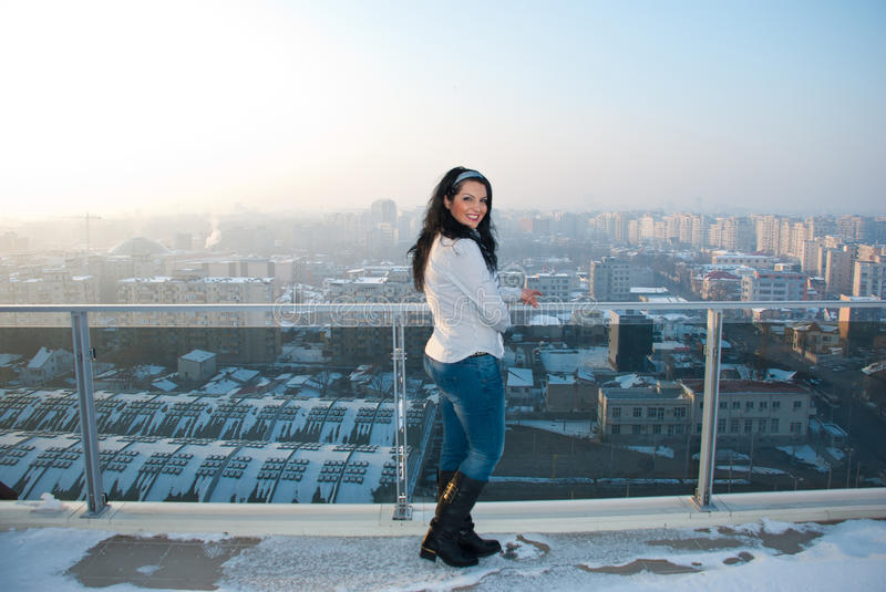 Woman on balcony with city view. Woman outdoor on a apartment balcony with city view in winter stock photos