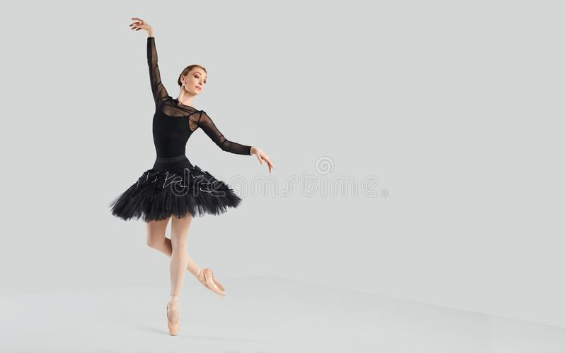 Woman ballet dancer over gray background. royalty free stock image
