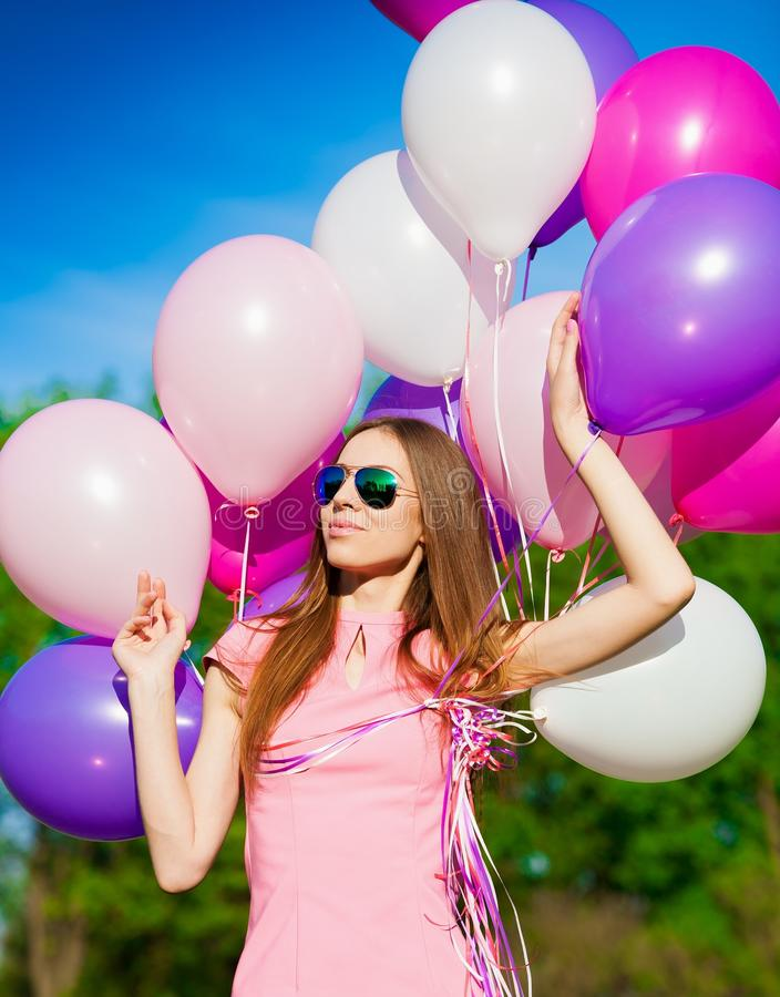 Woman balloons, close up, forest. Beautiful fun woman holding multicolored helium balloons. Has smiling face, long hair, clothed pink dress, sunglasses. Has slim stock images