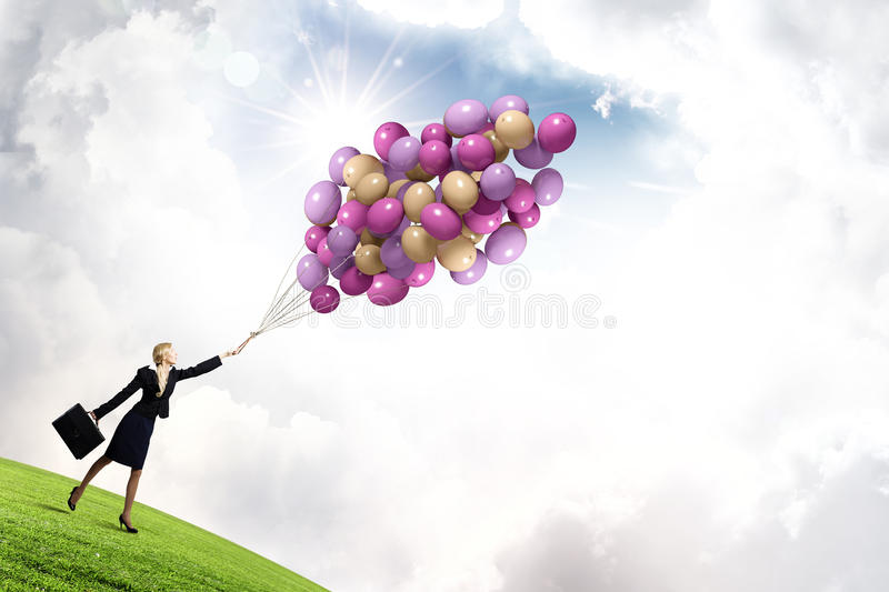 Woman with balloons. Young businesswoman with suitcase and bunch of colorful balloons stock image