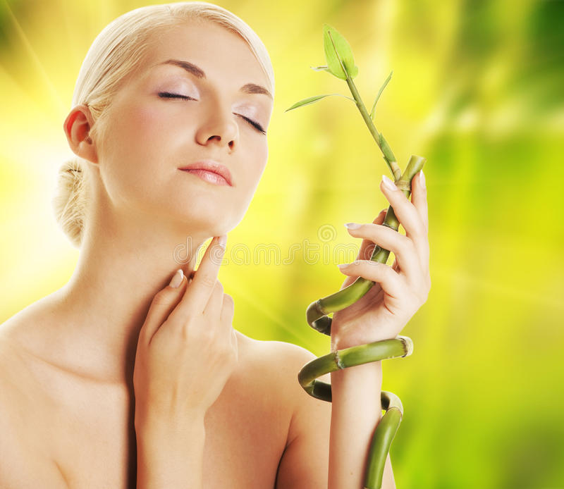 Woman with a bamboo plant. Beautiful young woman with a bamboo plant stock photography
